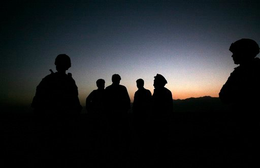 In this Sunday, Oct. 18, 2009 file photo, U.S. Army soldiers stand with Afghan policemen before a joint patrol of Qalanderkhail, outside of Bagram Air Field in Afghanistan. An Afghan official says that a suicide bomber has killed three foreign troops in