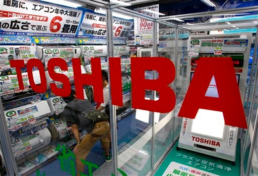 In this July 20, 2015 file photo, shoppers watch air conditioners displayed at an electronics store in Tokyo.