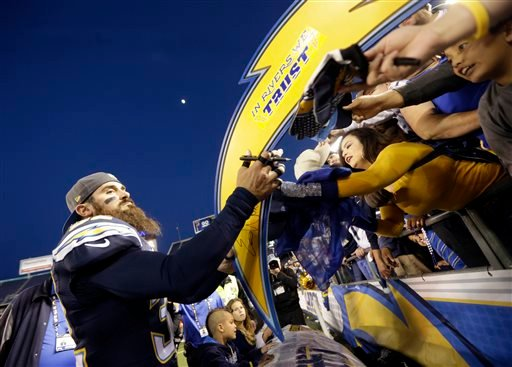 San Diego Chargers free safety Eric Weddle signs autographs after their win against the Miami Dolphins during the second half in an NFL football game Sunday, Dec. 20, 2015, in San Diego. (AP Photo/Lenny Ignelzi)