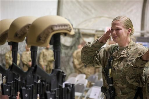 A U.S. service member salutes her fallen comrades during a memorial ceremony for six Airmen killed in a suicide attack, at Bagram Air Field, Afghanistan on Wednesday, Dec. 23, 2015. The deadliest attack in Afghanistan since 2013 killed six U.S. troops on