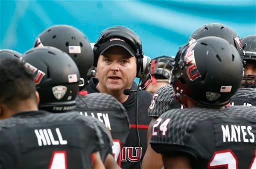 Northern Illinois coach Rod Carey talks to his team during a timeout in the first half of the Poinsettia Bowl NCAA college football game against Boise State on Wednesday, Dec. 23, 2015, in San Diego. (AP Photo/Lenny Ignelzi)