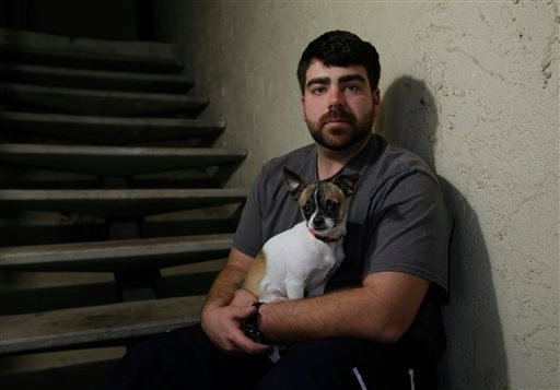 """In this photo taken Thursday, Dec. 17, 2015, Josh Redmyer, a former Marine who served three tours in Iraq, poses with Milo, who he calls his """"therapy dog,"""" in Oroville, Calif. Redmyer, who was diagnosed with Post-Traumatic Stress Disorder in 2009, receive"""