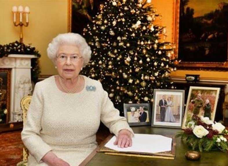 In this Dec. 10, 2015 photo, Britain's Queen Elizabeth II sits at a desk in the 18th Century Room in Buckingham Palace in London, after recording her Christmas Day broadcast to the Commonwealth, to be broadcast Friday, Dec. 25, 2015.  AP