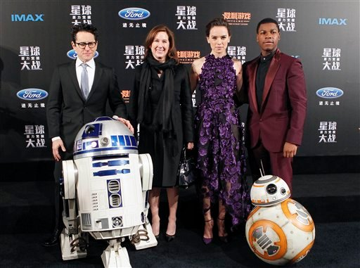 "From left, director J.J. Abrams, producer Kathleen Kennedy, actress Daisy Ridley and actor John Boyega pose with droids character BB-8 and R2-D2 on stage during the premiere of ""Star Wars: The Force Awakens"" in Shanghai, China, Sunday, Dec. 27, 2015. (Chi"