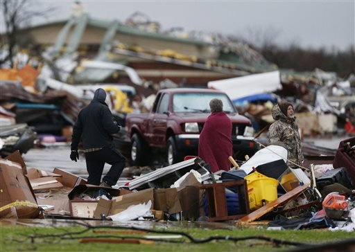 People assess the damage to a storage facility destroyed by Saturday's tornado in Garland, Texas, Sunday, Dec. 27, 2015. Tornadoes that swept through the Dallas area caused substantial damage and at least 11 people died either from the storm or related tr