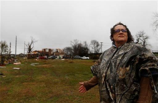 Evelyn Lindstrom looks for her cat that ran away as her home, seen behind her, was damaged by Saturday night's tornado in Copeville, Texas, Sunday, Dec. 27, 2015. Tornadoes that swept through the Dallas area caused substantial damage and at least 11 peopl