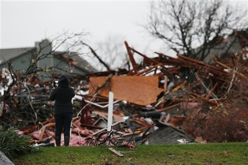 Residents take a picture near a pile of debris at an apartment complex damaged by Saturday night's tornado in Garland, Texas, Sunday, Dec. 27, 2015. Tornadoes that swept through the Dallas area caused substantial damage and at least 11 people died either
