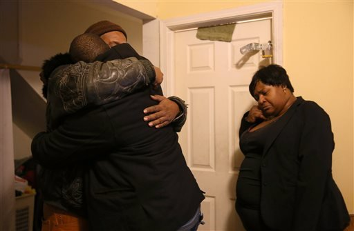 Melvin Jones, facing camera, hugs Robin Andrews, both brothers of Bettie Jones, 55, in Jones' living room after she was shot and killed by a Chicago police officer in Chicago on Saturday, Dec. 26, 2015. A Chicago police officer shot and killed Jones and a