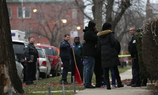Chicago police officers talk with relatives of one of the two people killed by a police officer, as they investigate a shooting in the entry of their apartment in Chicago on Saturday, Dec. 26, 2015. A Chicago police officer shot and killed two people whil