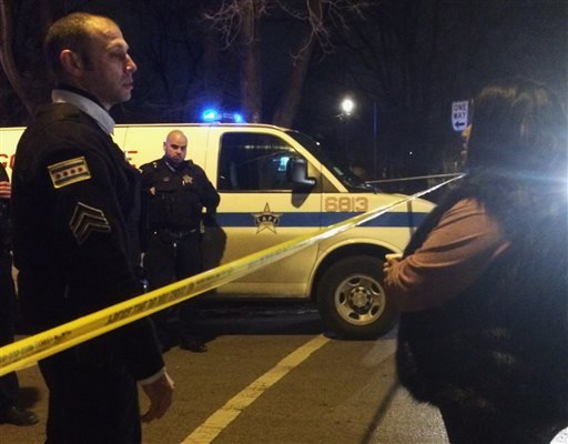 A Chicago police sergeant speaks with a relative of a man who was killed by a police officer in the West Garfield Park neighborhood in Chicago, early Saturday, Dec. 26, 2015. A Chicago police officer shot and killed two people while responding to a domest