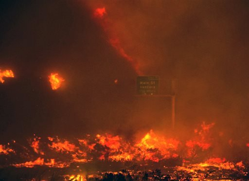 In this photo provided by Diego Topete, fire overruns the state Highway 101 near Ventura, Calif., Saturday, Dec. 26, 2015. The wind-whipped wildfire closed a major coastal highway in Southern California and forced dozens of homes to be evacuated, authorit