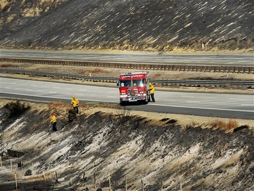 Firefighters look over a burned area along Highway 101 in Ventura, Calif., Saturday, Dec. 26, 2015. A wind-whipped wildfire closed a major coastal highway in Southern California and forced dozens of homes to be evacuated, authorities said Saturday. No inj