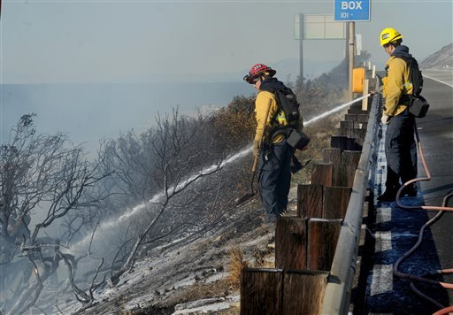 Ventura County Fire Department firefighters spray a hot spot along Highway 101 in Ventura, Calif., Saturday, Dec. 26, 2015. A wind-whipped wildfire closed a major coastal highway in Southern California and forced dozens of homes to be evacuated, authoriti