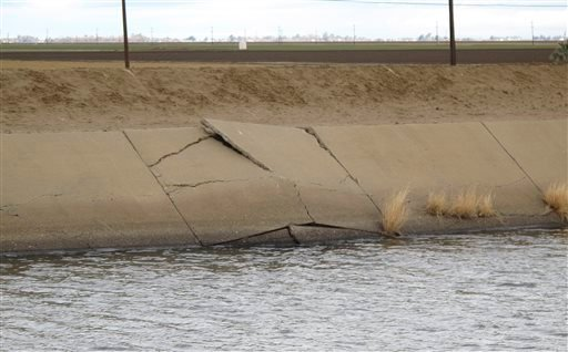 This Dec. 22, 2015, photog shows a buckle in the lining of the Delta Mendota Canal near Dos Palos, California, caused by sinking land. Four years of drought and heavy reliance on pumping of groundwater have made the land sink faster than ever up and down