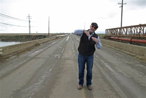 In this Dec. 22, 2015 photo, Chris White, general manager of the Central California Irrigation District, speaks during an interview with The Associated Press as he stands on a bridge over the Outside Canal near Dos Palos, Calif., that needs to be replaced