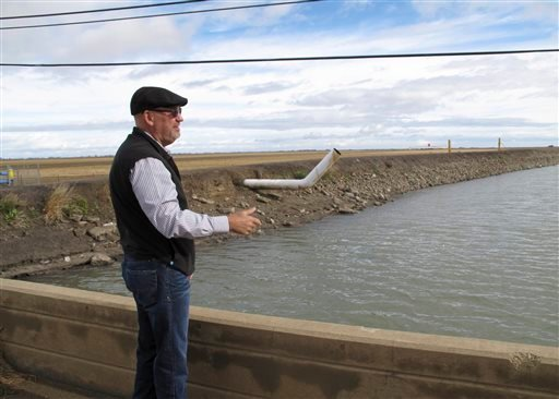 In this Dec. 22, 2015, photo, Chris White, general manager of the Central California Irrigation District, explains the expense of sinking land near Dos Palos, California. Four years of drought and heavy reliance on pumping of groundwater have made the lan