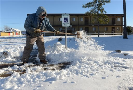 Ismael Avelar, maintenance employee for the Village Place Apartments, shovels snow Monday morning, Dec. 28, 2015, from the walkway to the apartment complex office in Odessa, Texas. As much as 7 inches of snow fell over the weekend in Odessa and many busin
