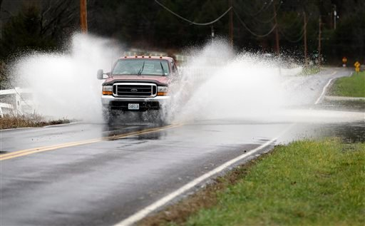 The driver of a pickup truck crosses a flooded section of road Monday, Dec. 28, 2015, in Eureka, Mo. Missouri Gov. Jay Nixon has declared a state of emergency due to wide spread flooding around the state that has closed many roads after a storm system dro