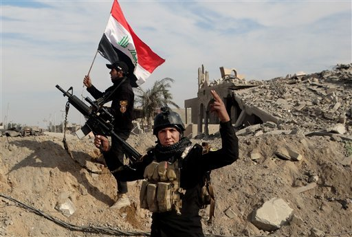 In this Sunday, Dec. 27, 2015 photo, Iraqi security forces raise an Iraqi flag near the provincial council building in central Ramadi, 70 miles (115 kilometers) west of Baghdad. Iraqi military forces on Monday retook a strategic government complex in the