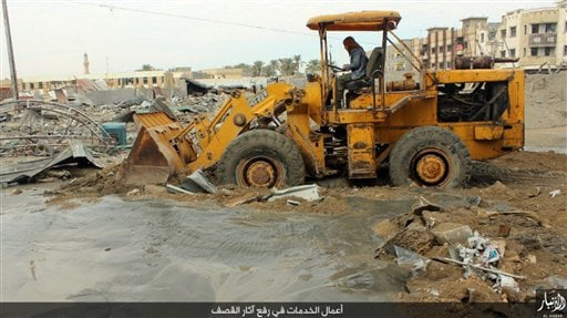 This image posted online Sunday, Dec. 27, 2015, by supporters of the Islamic State militant group on an anonymous photo sharing website, shows a fighter cleaning up heavy damage in Ramadi, Iraq, a day before Iraqi forces backed by U.S.-led airstrikes, re-