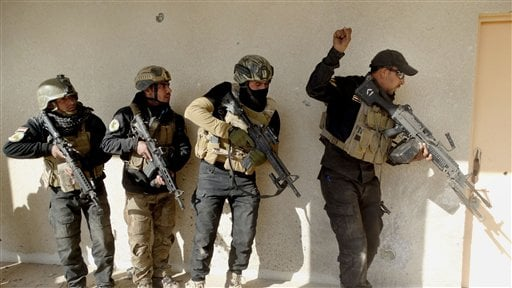 In this Sunday, Dec. 27, 2015 photo, Iraqi security forces search a building in the government complex in central Ramadi, 70 miles (115 kilometers) west of Baghdad, Iraq. Iraqi military forces on Monday retook a strategic government complex in the city of