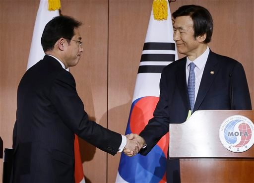 South Korean Foreign Minister Yun Byung-se, right, shakes hands with his Japanese counterpart Fumio Kishida after their joint press conference at Foreign Ministry in Seoul, South Korea, Monday, Dec. 28, 2015. The foreign ministers said they had reached a