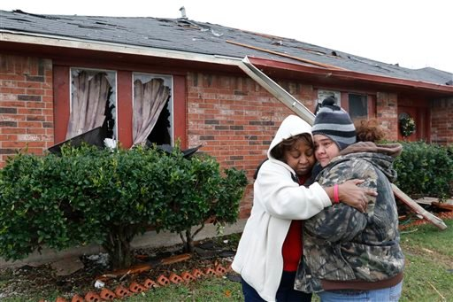 Roberta Moses, left, and Monica Holman embrace in Roberta's storm-damaged front yard in Glenn Heights, Texas, Monday, Dec. 28, 2015. (David Woo/The Dallas Morning News via AP)