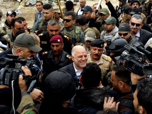 Iraqi Prime Minister Haider al-Abadi, center, smiles as he tours the city of Ramadi after it was retaken by the security forces in Ramadi, 70 miles (115 kilometers) west of Baghdad, Iraq, Tuesday, Dec. 29, 2015. Iraqi military forces on Monday retook a st