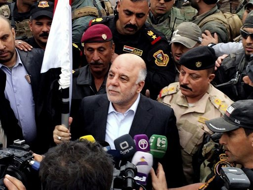 Iraqi Prime Minister Haider al-Abadi, center, raises an Iraqi flag in the city of Ramadi after it was retaken by the security forces in Ramadi, 70 miles (115 kilometers) west of Baghdad, Iraq, Tuesday, Dec. 29, 2015. Iraqi military forces on Monday retook