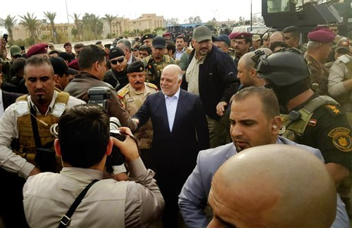 Iraqi Prime Minister Haider al-Abadi, center, tours the city of Ramadi after it was retaken by the security forces in Ramadi, 70 miles (115 kilometers) west of Baghdad, Iraq, Tuesday, Dec. 29, 2015. Iraqi military forces on Monday retook a strategic gover