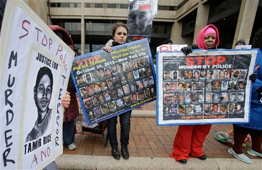 People protest outside the Cuyahoga County Justice Center, Tuesday, Dec. 29, 2015, in Cleveland. People marched peacefully in front of the Justice Center in downtown Cleveland to protest a grand jury's decision not to indict two white Cleveland police off