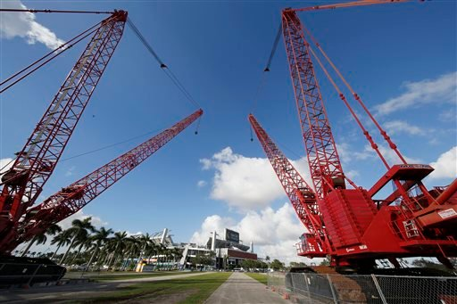 Large construction cranes sit in the parking lot of Sun Life Stadium Tuesday, Dec. 29, 2015, in Miami Gardens Fla.