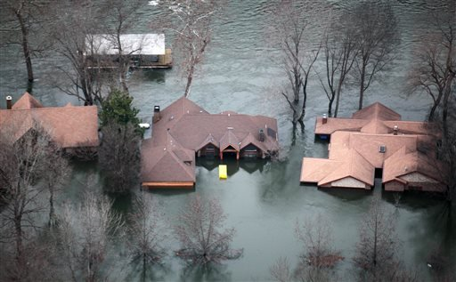In this Tuesday, Dec. 29, 2015 photo, floodwaters from Lake Taneycomo surrounded several homes in a Branson, Mo., neighborhood after a record amount of water was released from the Table Rock Lake Dam.