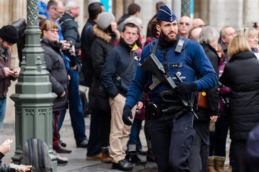 An armed police man patrols at the Grand Place in Brussels on Tuesday, Dec. 29, 2015. Two people have been arrested in Belgium on suspicion of planning attacks in Brussels during the holidays, the federal prosecutor's office said Tuesday. A source close t