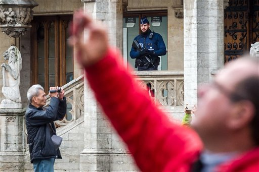 Tourists make pictures as an armed policeman guards the Grand Place in Brussels on Tuesday, Dec. 29, 2015. Two people have been arrested in Belgium on suspicion of planning attacks in Brussels during the holidays, the federal prosecutor's office said Tues