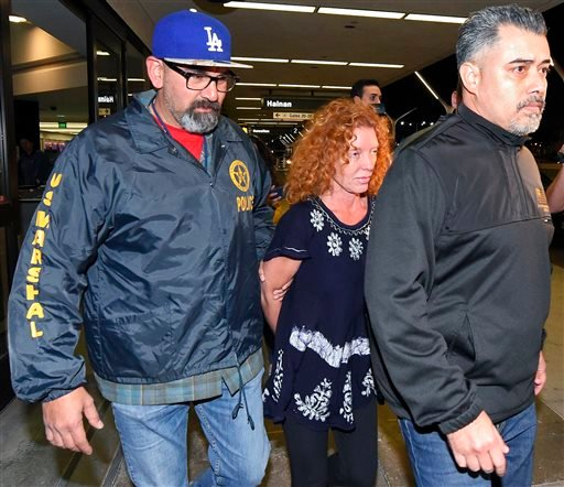 Tonya Couch, center, is taken by authorities to a waiting car after arriving at Los Angeles International Airport, Thursday, Dec. 31, 2015, in Los Angeles.