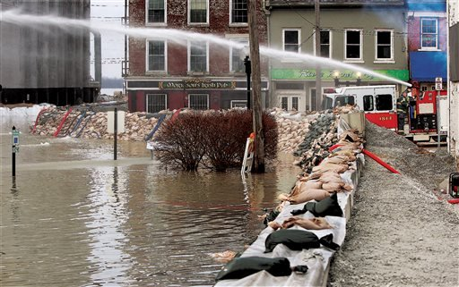 Firemen spray water towards water seepage under the city's makeshift flood levee in downtown Alton, Ill., Wednesday, Dec. 30, 2015.