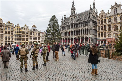 Belgian soldiers patrol as tourists visit the Grand Place in Brussels on Tuesday, Dec. 29, 2015. Two people have been arrested in Belgium on suspicion of planning attacks in Brussels during the holidays, the federal prosecutor's office said Tuesday. A sou