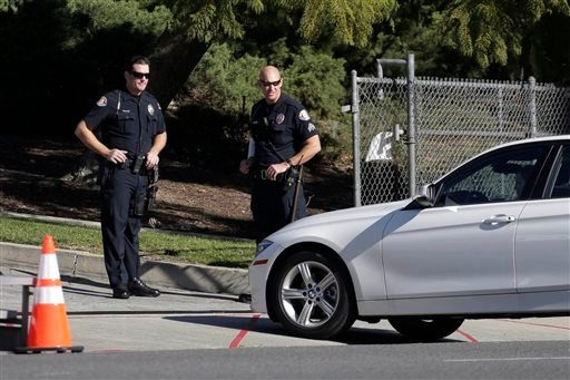 Two Pasadena police officers inspect a vehicle on Colorado Blvd on the route of the Rose Parade in Pasadena, Calif., Thursday, Dec. 31, 2015. (AP Photo/Nick Ut)