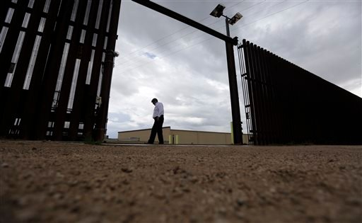 Sept. 15, 2015, photo, Othal Brand Jr., general manager of Hidalgo County Water Improvement District, walks along a gate in the border fence that run along the water plant, in Hidalgo, Texas. (AP Photo/Eric Gay)