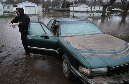 Thomas Barnard removes the registration from fiancee Jessica Klick's 1995 Buick after floodwaters from the South Fork of the Sangamon River receded during a visit to the couple's home in Kincaid, Ill., Thursday, Dec. 31, 2015. (David Spencer/The State Jou