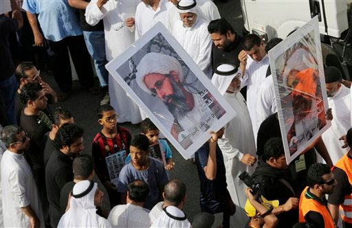 In this Saturday, May 30, 2015, photo, Saudis carry a poster demanding freedom for jailed Shiite cleric Sheikh Nimr al-Nimr, during a funeral procession, in Tarut, Saudi Arabia. (AP Photo/Hasan Jamali)
