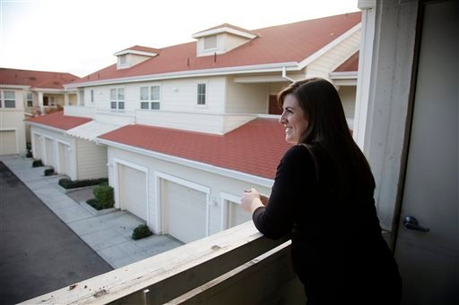 In this Dec. 11, 2015, photo, Katy Howser, a kindergarten teacher in the Santa Clara School District, looks out from the balcony of her apartment at Casa Del Maestro, an apartment complex for teachers, in Santa Clara, Calif. (AP Photo/Marcio Jose Sanchez)