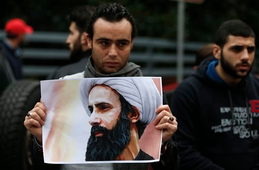 A Lebanese protester holds a picture of the Saudi Shiite cleric Sheikh Nimr al-Nimr during a protest to denounce his execution, in front of the Saudi Arabian embassy in Beirut, Lebanon, Sunday, Jan. 3, 2016. Hassan Nasrallah, the leader of the Lebanese Sh