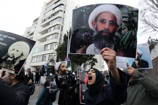 Iranian and Turkish demonstrators hold pictures of Shiite cleric Sheikh Nimr al-Nimr as they protest outside the Saudi Embassy in Ankara, Turkey, Sunday, Jan. 3, 2016, following Saudi Arabia's execution of 47 prisoners in one day. Saudi Arabia announced t