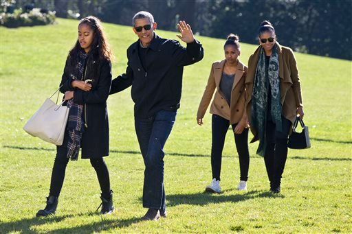 President Barack Obama waves as he walks across the South Lawn with daughter Malia, left, followed by Sasha Obama and first lady Michelle Obama, on their return to the White House, in Washington, Sunday, Jan. 3, 2016, after a family vacation in Hawaii. (A