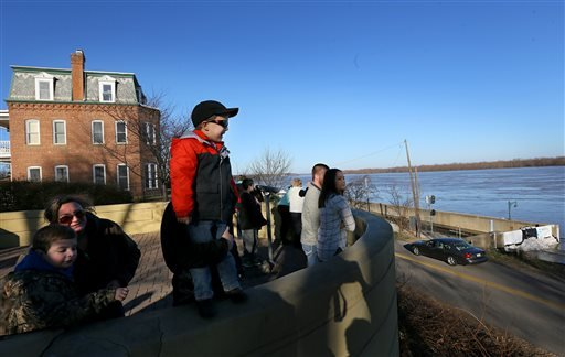 Ty Burch, from left, 6, mother Casey, brother Brody, 4, and father Keith, behind Brody, look out over the swollen Mississippi River floodwater rushing by Cape Girardeau, Mo., Saturday, Jan. 2, 2016. Missouri Gov. Jay Nixon stopped in Cape Girardeau, where