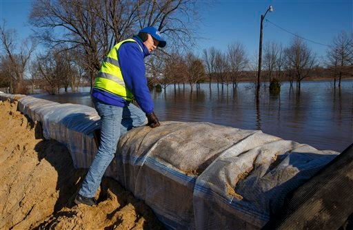 Petersburg, Ill., Mayor John Stiltz climbs the nearly 2,000-foot long wall erected to protect the town's business district from the Sangamon River on Saturday, Jan. 2, 2016. Illinois Gov. Bruce Rauner of Illinois also toured flood-ravaged areas Saturday a
