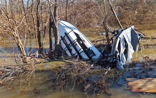 Boats with covers and trailers are fetched up in Meramec River floodwater on Friday, Jan. 1, 2016, just north of Interstate 44 in Eureka, Mo., near Route 66 State Park. The worst of the dangerous, deadly winter flood is over in the St. Louis area, leaving