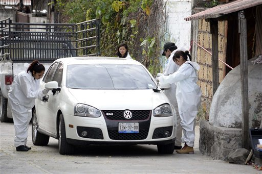 Forensic investigators inspect a car outside the home where Gisela Mota was killed, one day after taking office as mayor, in Temixco, Morelos State, Mexico, Saturday, Jan. 2, 2016. The Morelos state Public Security Commission says attackers invaded Mota's
